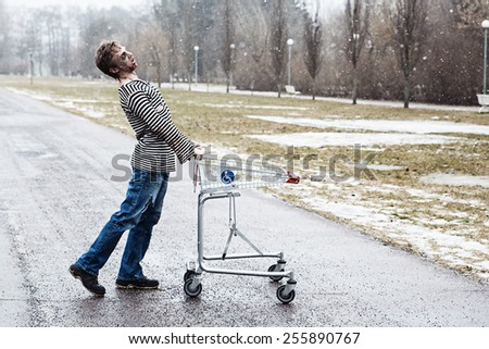 Strangely walking guy with a shopping wagon - stock photo