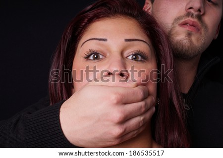 stranger covering the mouth of a terrified girl - stock photo