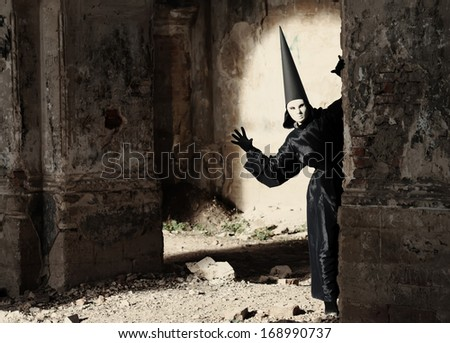 Stranger in white mask looking around the corner in an old ruined building - stock photo