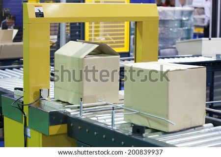 Strapping Machine for Industrail Packaging Line - stock photo