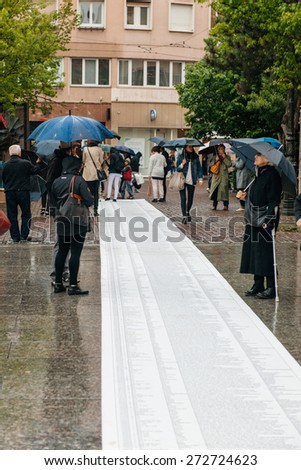 STRASBOURG- APR 26 2015: People reading long list of death person at demonstration protest against immigration policy and border management - stock photo