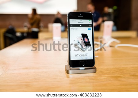 STRASBOURG, FRANCE - APR 9, 2016: New iPhone SE in docking station with Apple.com page opened. New Apple iPhone tends to become one of the most popular smart phones in the world. - stock photo