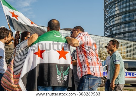 STRASBOURG, FRANCE - AUG 20, 2015: People protesting in front of European Parliament denouncing the Syrian airstrikes on Douma wheremore 80 were killed - people holding wearing Syrian flag - stock photo