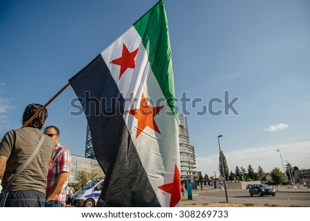 STRASBOURG, FRANCE - AUG 20, 2015: People protesting in front of European Parliament denouncing the Syrian airstrikes on Douma wheremore 80 were killed - man holding flag of Syria - stock photo