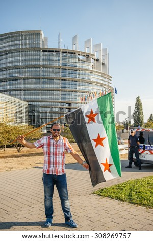 STRASBOURG, FRANCE - AUG 20, 2015: People protesting in front of European Parliament denouncing the Syrian airstrikes on Douma - man holding syrian flag Parliament building in the background - stock photo