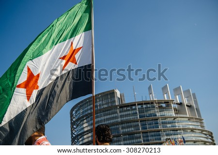 STRASBOURG, FRANCE - AUG 20, 2015: People protesting in front of European Parliament denouncing the Syrian airstrikes on Douma  - flag of Syria with Parliament building in the background - stock photo