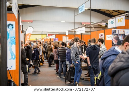 STRASBOURG, FRANCE - FEB 4, 2016: Children and teens of all ages attending annual Education Fair to choose career path and receive vocational counseling - rows of college stands - stock photo