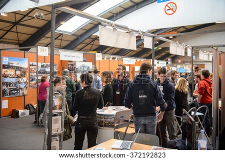 STRASBOURG, FRANCE - FEB 4, 2016: Children and teens of all ages attending annual Education Fair to choose career path and receive vocational counseling - busy college stand - stock photo