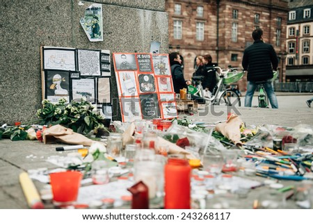 STRASBOURG, FRANCE - 10 JAN, 2015: Light candles and pencils near General Kleber statue in tribute to the victims of the terrorist attacks in Paris on January 11, 2015 - stock photo