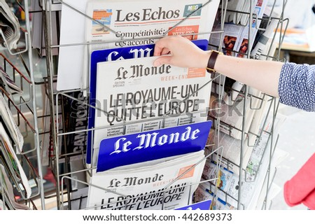 STRASBOURG, FRANCE - JUN 25, 2016: Woman buying Le Monde newspaper with shocking headline titles at press kiosk about the Brexit referendum in United Kingdom requesting to quit the European Union - stock photo