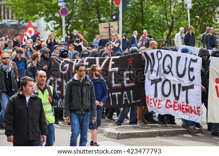 STRASBOURG, FRANCE - MAY 19, 2016: Group of youg people with covered faces holding placards walk with crowd during a demonstrations against proposed French government's labor and employment law reform - stock photo