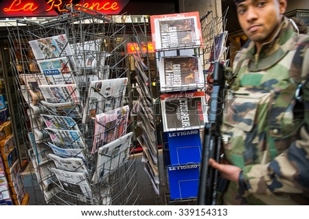 STRASBOURG, FRANCE - 14 NOV 2015 French solider walking in front of the Press Kiosk with the front covers International newspapers display headlining terrorist attacks yesterday in Paris peaceforparis - stock photo