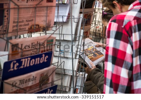STRASBOURG, FRANCE - 14 NOV, 2015: People reading front kovers at press kiosk of International newspapers display headlining the terrorist attacks yesterday in Paris - stock photo