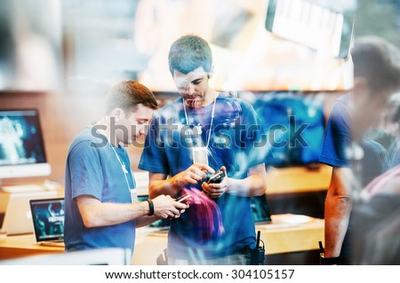 STRASBOURG, FRANCE - SEPTEMBER 19, 2014: Apple Store interior reflected with customers waiting in line outside in front the store during the sales launch of the iPhone 6 and iPhone 6 Plus - stock photo