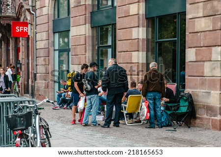 STRASBOURG, FRANCE - SEPTEMBER 18, 2014: People waits in line for the launch of the new iPhone 6 and iPhone 6 Plus in Strasbourg, France, on September 18. New iPhones goes on sale on September 19 - stock photo