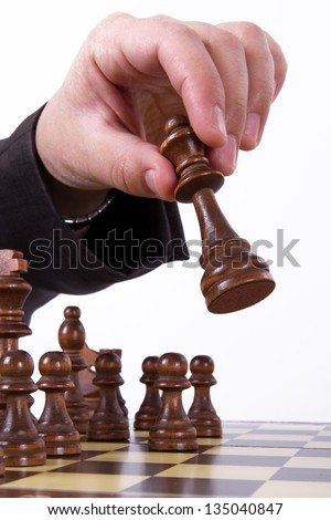 Strategy concept, businessman hand moving queen on chess board, isolated on white background. - stock photo