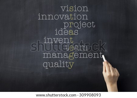 Strategy word puzzle on blackboard with words vision, innovation, project, ideas, invent, team, management and quality. Businesswoman holding a chalk. - stock photo