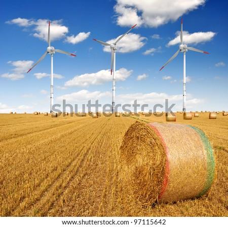 Straw bales on farmland with wind turbine on blue cloudy sky - stock photo