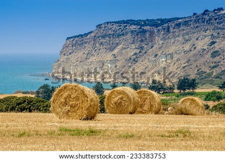 Straw bales on the field against Mediterranean sea and mountain  in Cyprus. - stock photo