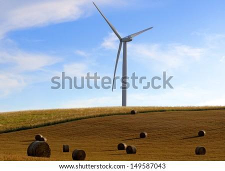 straw bales on wind turbines background - stock photo