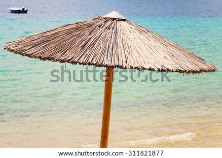 Straw Beach Umbrella and boat against blue sea,ocean. Summer, holiday, vacation background - stock photo