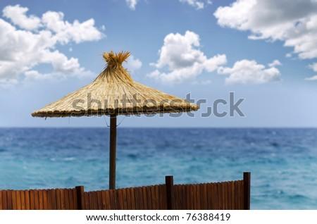 Straw beach umbrella with beautiful cloudscape background - stock photo