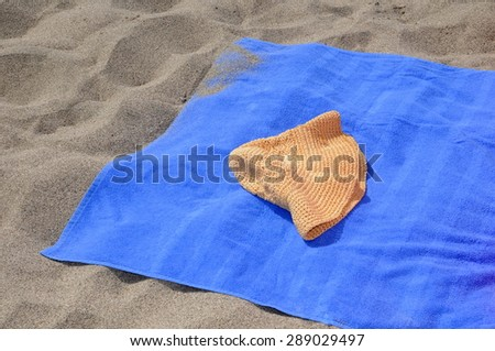Straw hat and blue towel on a sunny beach - stock photo