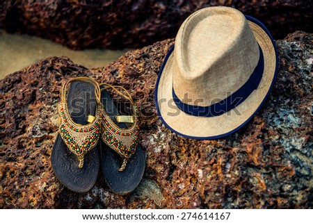 Straw hat and flip flops on a tropical beach, vacation on the sea, Goa, India - stock photo