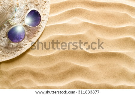 Straw hat and sunglasses on beach sand - stock photo