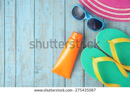 Straw hat and sunglasses on blue wood.Summer holiday background concept - stock photo