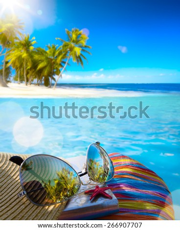 Straw hat, bag and sun glasses  on a tropical beach background - stock photo