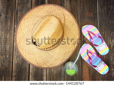 straw hat, flip flops and cold drink on wooden background - stock photo