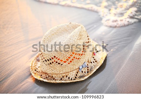 Straw hat laying on the seaside at sunset - stock photo