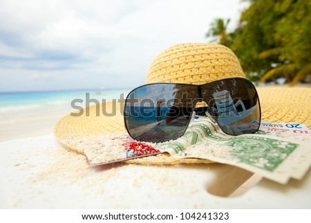 Straw hat, money, bank card, shades with relaxing woman mirrored in it - stock photo