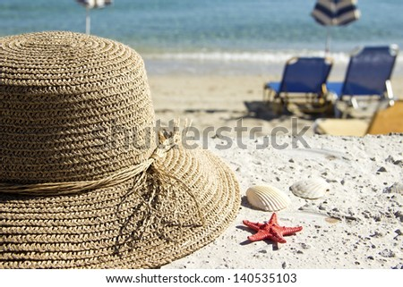 Straw hat on the beach with seashells and starfish - stock photo