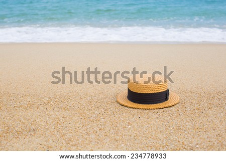 straw hat on the shore of a beach - stock photo