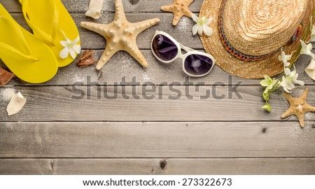 Straw hat,sunglasses and beach slippers on wood - stock photo