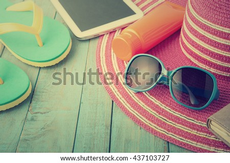Straw hat tablet and sunglasses on blue wood.Summer holiday background concept.Vintage Tone - stock photo