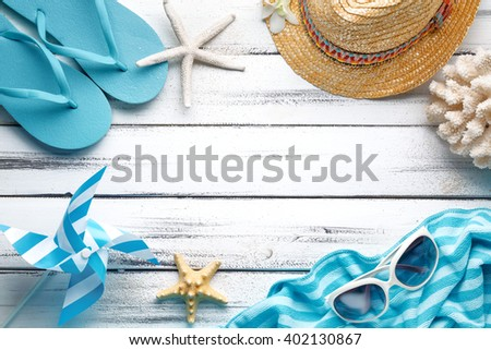 Straw hat,towel and beach slippers on wood   - stock photo
