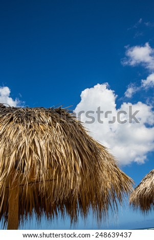 Straw hut at beach with vivid blue sky and clouds in background. - stock photo