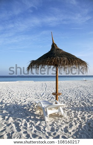 Straw parasol providing shade on the beach - stock photo