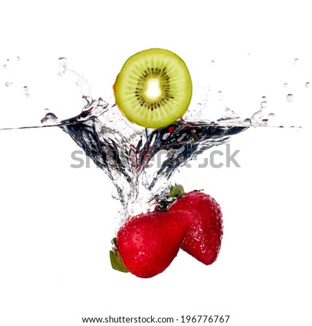 Strawberries and kiwi falling into clear water isolated on white background. Closeup of fresh and health fruit - stock photo