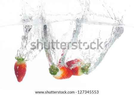 Strawberries are thrown into a bowl of fresh water. - stock photo