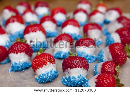 Strawberries dipped in white chocolate and marshmallow with blue sprinkles for the fourth of July. A creative treat with American colors. - stock photo