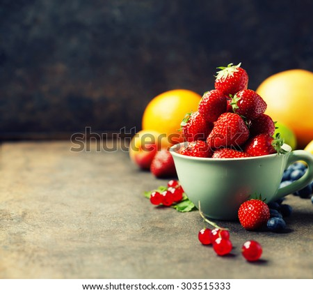 Strawberries in a cup and fresh fruits on rustic background - stock photo