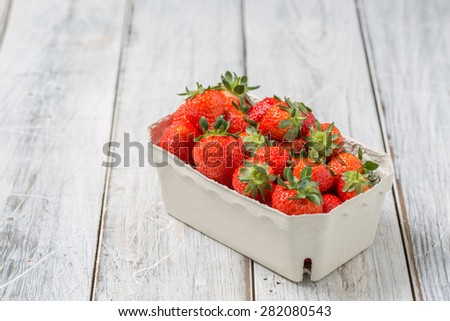 Strawberries in a paper bowl on a wooden table - stock photo