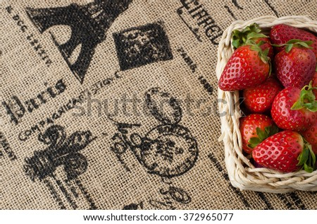 Strawberries in a small basket on the beige jute table cloth with French motif print - stock photo