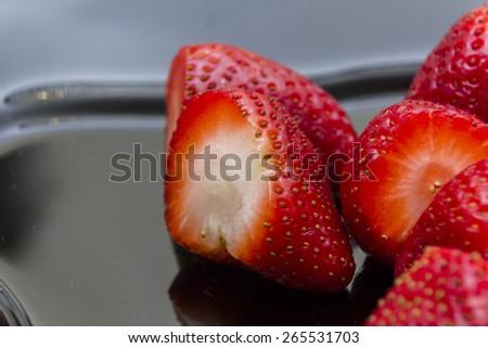 Strawberries in black ceramic plate - stock photo