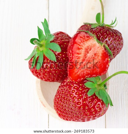 Strawberries in wooden spoon on white wooden background. - stock photo