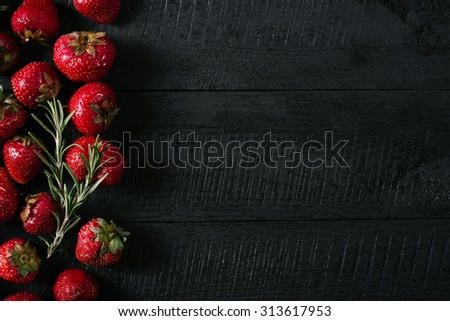 Strawberries on a black wooden background - stock photo